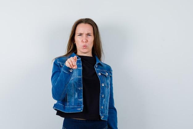 Молодая дама в блузке, пиджаке, указывая на камеру и нерешительно глядя, вид спереди.