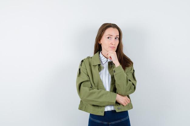ブラウスを着た若い女性、手にあごを支えるジャケット、夢のような正面図。