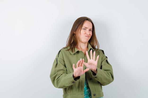 ブラウスの若い女性、停止ジェスチャーを示し、不快に見えるジャケット、正面図。