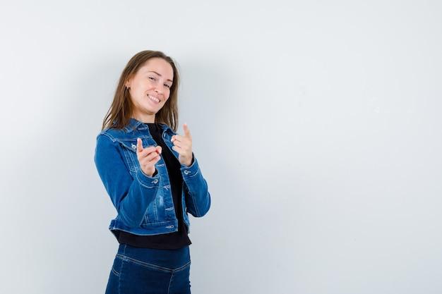 Молодая дама в блузке, указывая на камеру и уверенно глядя, вид спереди.