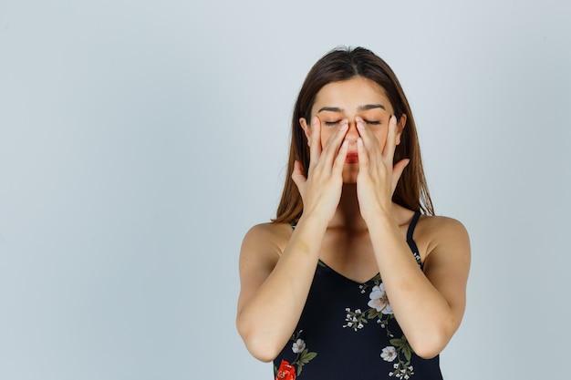 블라우스를 입은 젊은 여성이 코 주변에 얼굴 마스크를 문지르는 척하고 편안한 표정을 짓고 있습니다.