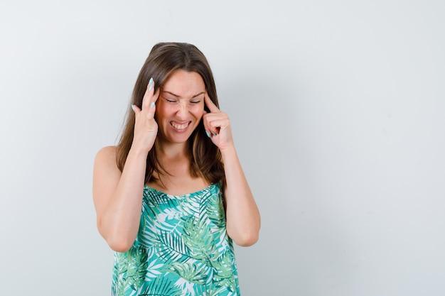 ブラウスでこめかみをこすり、疲れ果てた様子の若い女性、正面図。