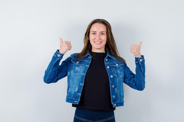 ブラウスの若い女性は、二重の親指を上に示し、自信を持って、正面図を表示します。