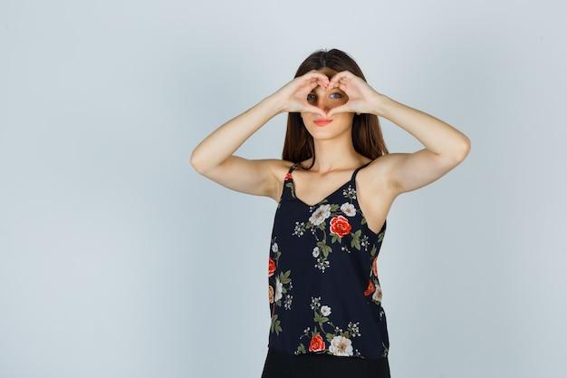 Молодая дама в блузке показывает жест сердца и выглядит уверенно, вид спереди.