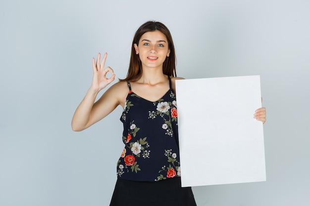 ブラウスの若い女性、空白のキャンバスを保持しているスカート、大丈夫なジェスチャーを示し、陽気に見える、正面図。