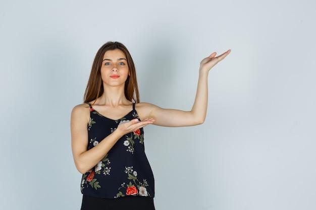 Молодая дама в блузке, юбке демонстрирует приветственный жест и уверенно выглядит, вид спереди.