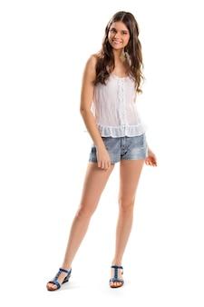 웃 고 블라우스에 젊은 아가씨. 파란색 반바지와 흰색 상의. 모델은 단순한 여름 복장을 입습니다. 면 옷과 가죽 샌들.