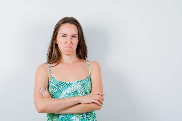顔をしかめ、怒っているように見えながら、腕を組んで立っているブラウスの若い女性、正面図。