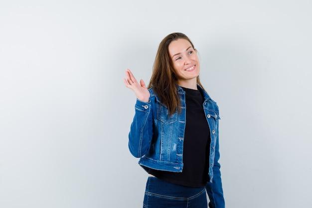 挨拶と陽気に見えるために手を振るブラウスの若い女性、正面図。