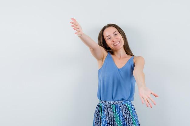 파란색 블라우스에 젊은 아가씨, 누군가를 포옹하고 유쾌한, 정면보기를 위해 팔을 여는 치마.