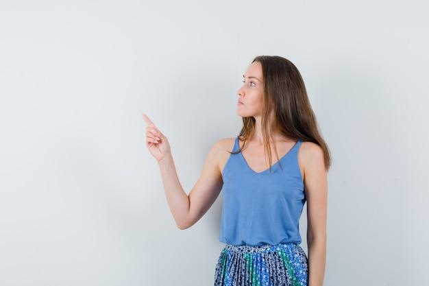 파란색 블라우스, 치마 제쳐두고 가리키는 찾고 초점, 전면보기 젊은 아가씨. 텍스트를위한 공간