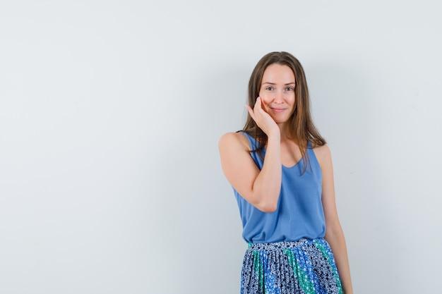 青いブラウスを着たお嬢様、カメラを見ながら頬に触れて印象的な正面図のスカート。テキスト用のスペース
