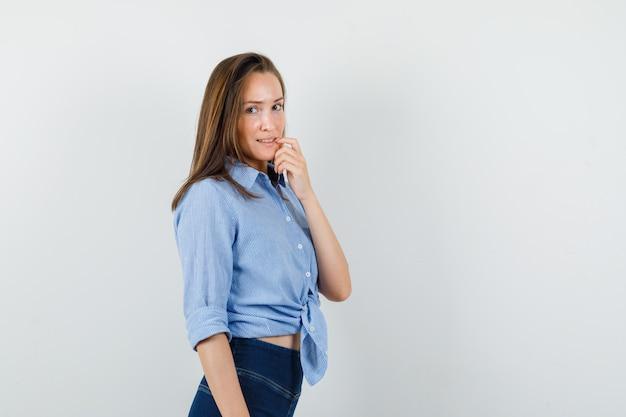 青いシャツを着た若い女性、唇に指を持って希望に満ちたパンツ