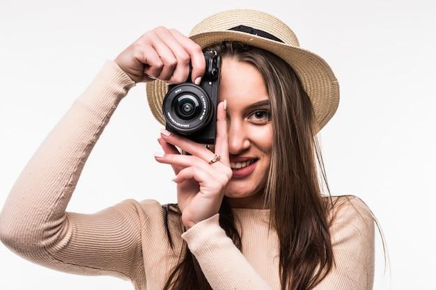 Девушка в яркой футболке и шляпе делает фото на ретро-камеру, изолированную на белом