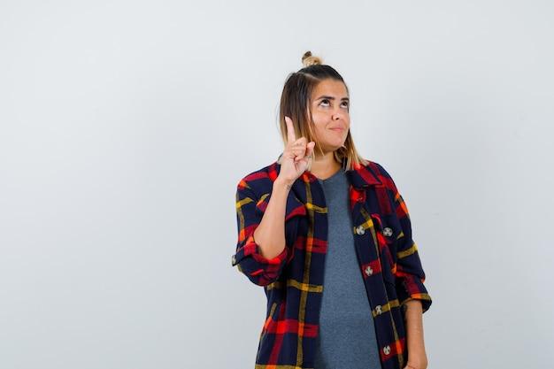 カジュアルなチェックシャツを着た若い女性が指で上を向いて注意深く見ている、正面図。