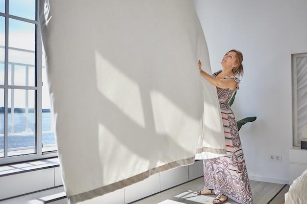 カジュアルなドレスを着た若い女性がカーテンを押し戻す