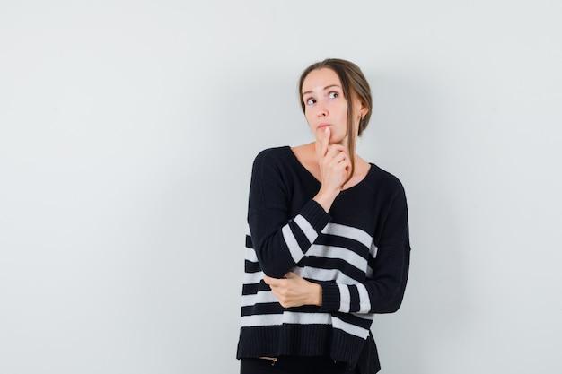 あごに指を持って物思いにふけるカジュアルなシャツの若い女性