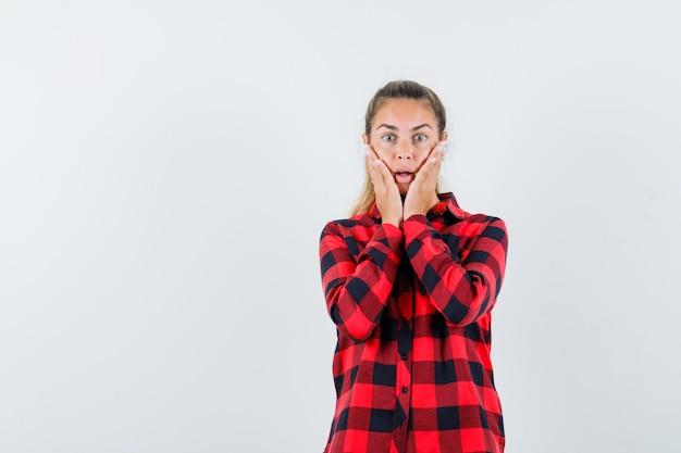 Молодая дама в повседневной рубашке, взявшись за руки на щеках и выглядя озабоченно, вид спереди.