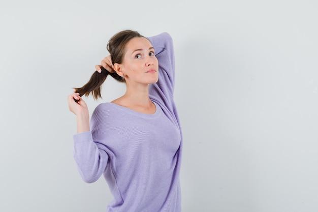 彼女のストランドを保持し、物思いにふけるカジュアルシャツの若い女性