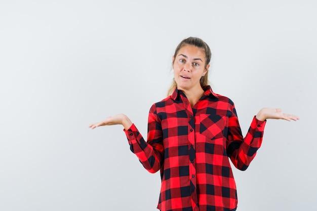 スケールジェスチャーを作成し、自信を持って、正面図を探しているカジュアルなシャツの若い女性。