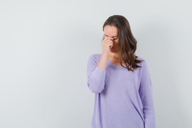 Девушка в повседневной рубашке протирает глаза и нос и выглядит усталой