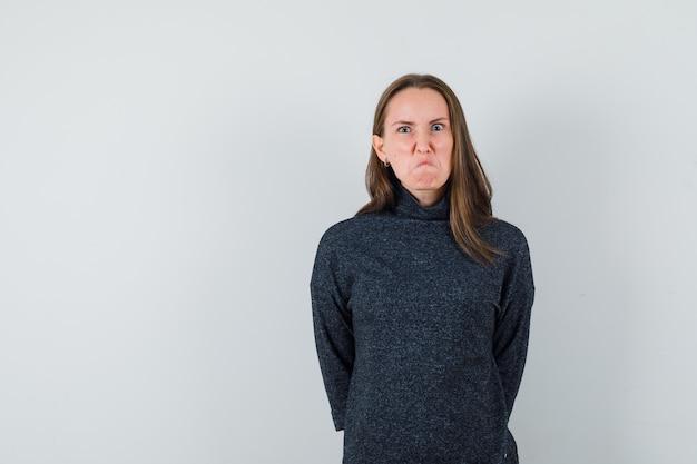 Молодая дама в повседневной рубашке хмурится и выглядит упрямой
