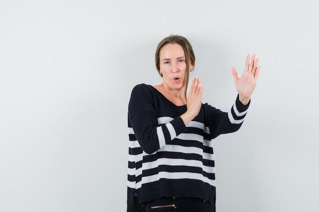 Молодая дама в повседневной рубашке демонстрирует жест каратэ и уверенно выглядит Бесплатные Фотографии