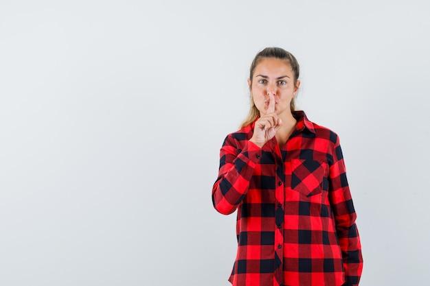 沈黙のジェスチャーを示し、自信を持って見えるカジュアルなシャツの若い女性、正面図。