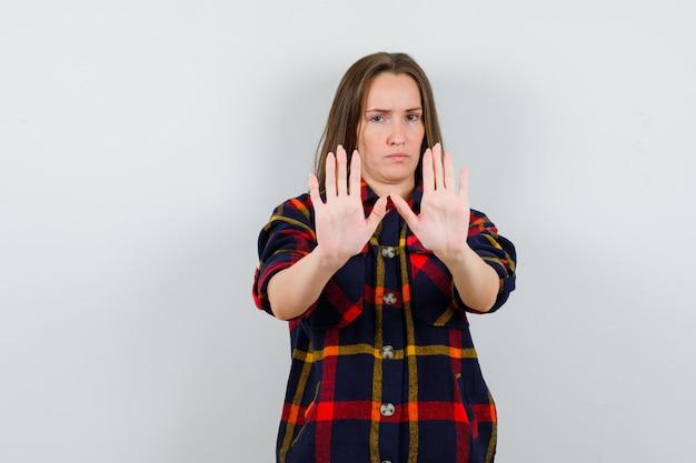 停止ジェスチャーを示し、毅然とした、正面図を示すカジュアルなシャツの若い女性。