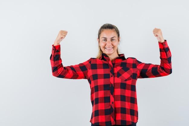 승자 제스처를 보여주는 행복, 전면보기를 찾고 캐주얼 셔츠에 젊은 아가씨.