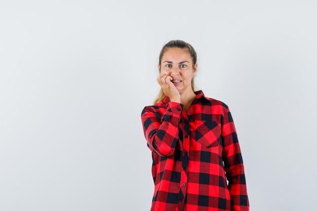 Молодая дама в повседневной рубашке, стоя в позе мышления и с тревогой глядя, вид спереди.