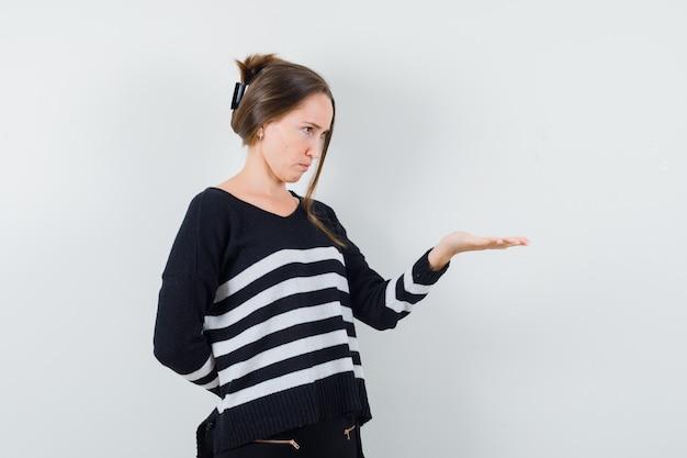 손을 스트레칭 하 고 혼란 스 러 워 보이는 캐주얼 셔츠에 젊은 아가씨