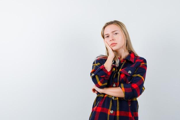 Молодая дама в клетчатой рубашке, взявшись за щеку и глядя задумчиво, вид спереди.