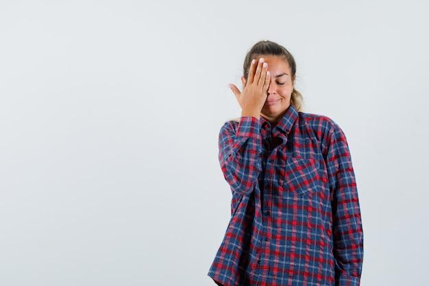 Молодая дама в клетчатой рубашке, взявшись за глаза и глядя мирно, вид спереди.