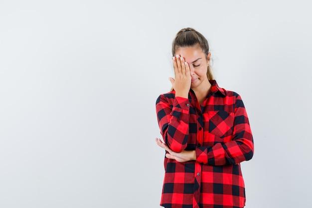 チェックシャツを着た若い女性が顔に手を握って疲れているように見える