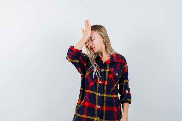 額に手を握り、忘れて見える、正面図のチェックシャツを着た若い女性。