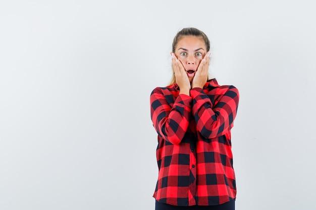 頬に手をつないで、ショックを受けているように見えるチェックシャツの若い女性
