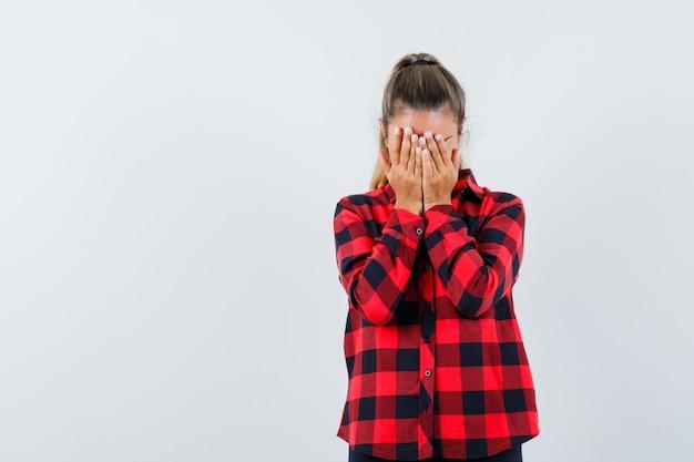 Молодая дама в клетчатой рубашке держится руками за лицо и выглядит печально