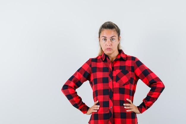 체크 셔츠에 젊은 아가씨 허리에 손을 잡고 의아해 찾고