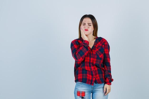 チェックシャツを着た若い女性、歯痛に苦しんでいるジーンズ、体調不良、正面図。