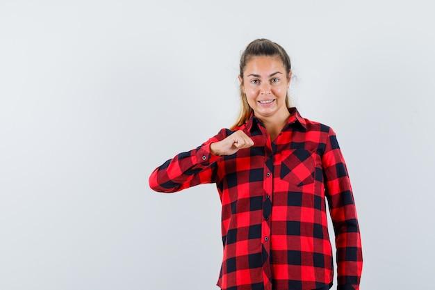 Молодая дама в клетчатой рубашке держит кулак и выглядит уверенно