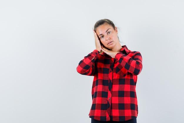 체크 셔츠에 젊은 아가씨 손바닥에 뺨을 기울고 우아한 찾고