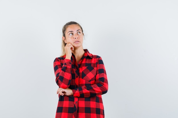 見上げて物思いにふけるチェックシャツの若い女性