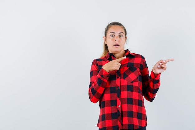 チェックシャツを着た若い女性が脇を向いて驚いて見える