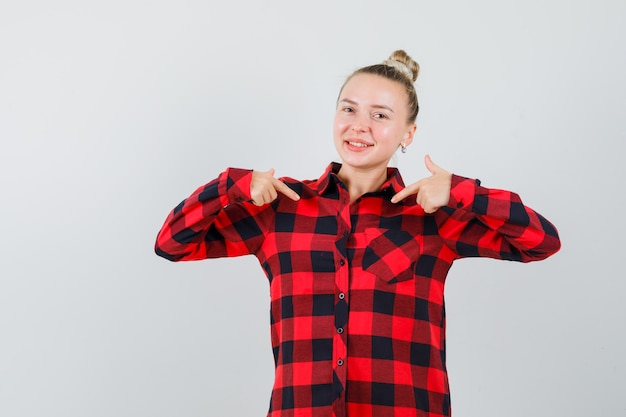 자신을 가리키고 자신감을 찾고 체크 셔츠에 젊은 아가씨