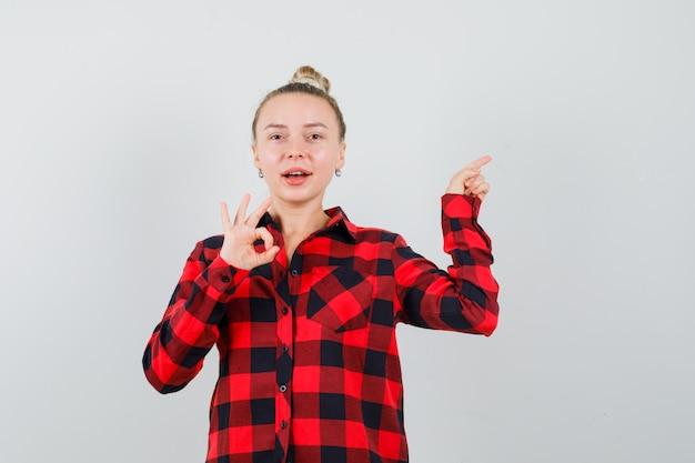 오른쪽 모서리를 가리키는 체크 셔츠에 젊은 아가씨, 확인 제스처를 표시하고 쾌활하게 보입니다.