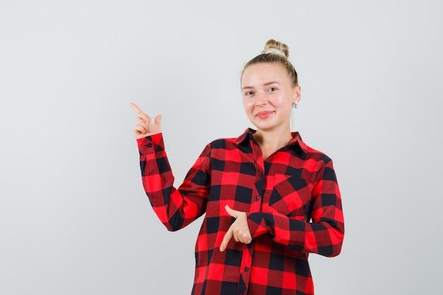 체크 셔츠에 젊은 아가씨가 손가락을 위아래로 가리키고 쾌활하게 보입니다.