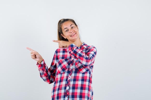 左側を指して幸せそうに見えるチェックシャツの若い女性、正面図。