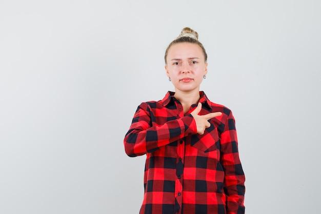 측면을 가리키고 불만을 찾고 체크 셔츠에 젊은 아가씨