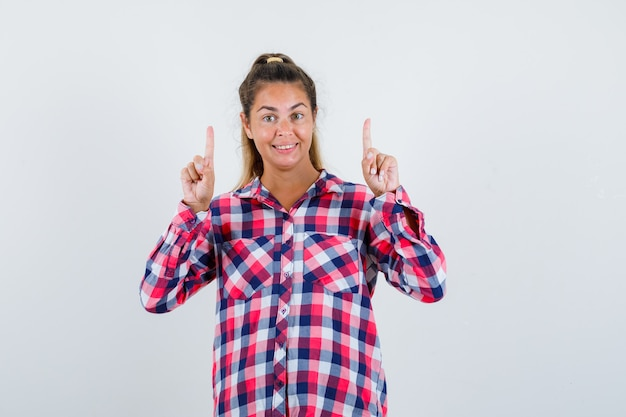 チェックシャツを着た若い女性が上を向いて幸せそうに見える、正面図。